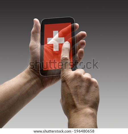 Holding Swiss flag screen smart phone. There is a route for hand and finger.  - stock photo