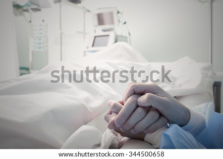 Holding the hand of a dying man in hospital - stock photo
