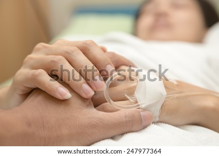 Holding the hand of a sick loved one in hospital bed - stock photo