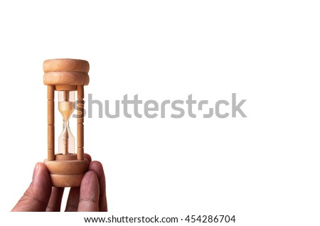 Holding the wooden classic hourglass; Isolated  - stock photo