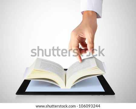 holding touch screen tablet and shows tablet in hand and open the book