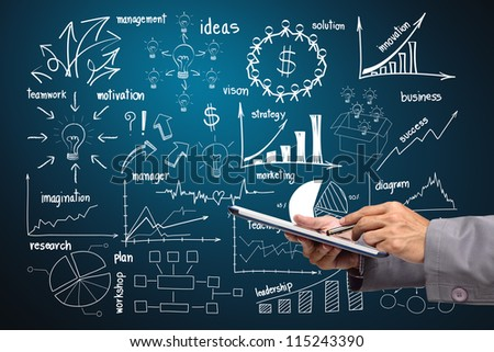 holding touch screen tablet With drawing business plan concept diagrams - stock photo
