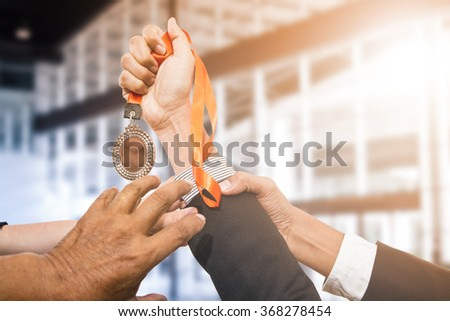 Holding winner's medal awards after successful with his business.  - stock photo