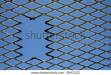 Hole in a fence against a blue sky - stock photo