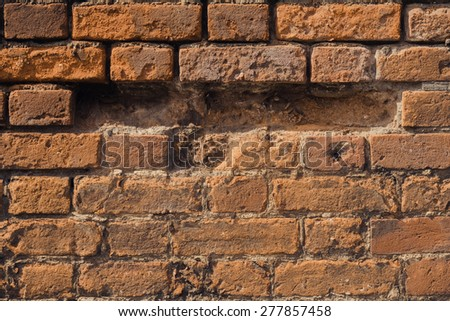 Hole in a weathered brick wall  closeup for background - stock photo