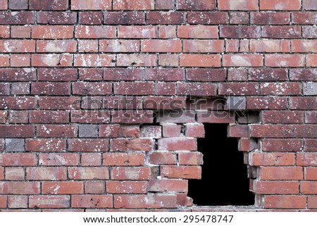 Hole in an old brick wall pattern showing damage to building