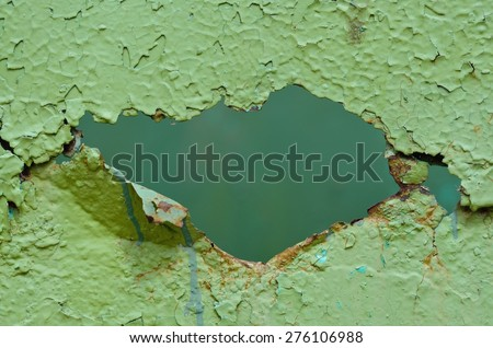 Hole in old metal wall painted green. Peeling paint, rust, many old layers. - stock photo