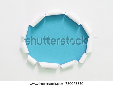 hole in paper on blue paper background, empty space for text.