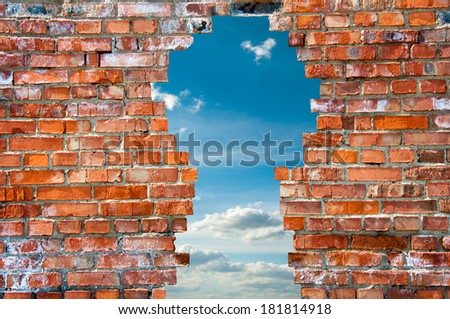 hole in the brick wall in the form of a keyhole - stock photo