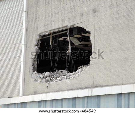 Hole in the wall of a building being demolished - stock photo