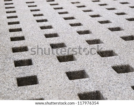 Hole Pattern in stone. The holes are arranged in a diagonal composition and are grouped into rows
