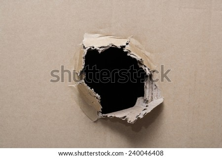 Hole ripped in brown paper - stock photo