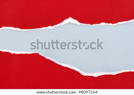 Hole ripped in red paper on blue background. Copy space