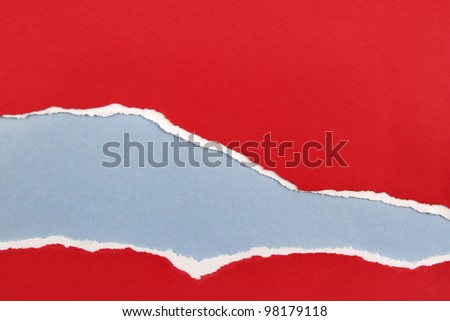 Hole ripped in red paper on blue background. Copy space - stock photo