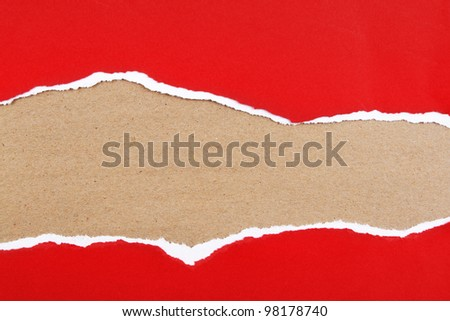 Hole ripped in red paper on brown background. Copy space - stock photo
