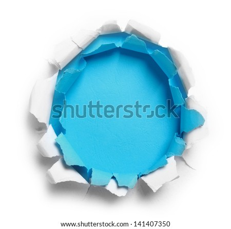 Hole ripped in white and blue paper on blue background