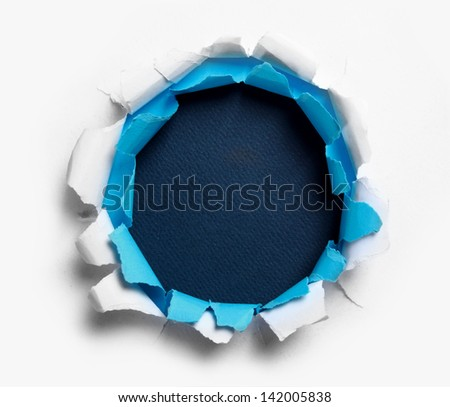 Hole ripped in white and blue paper on dark blue background
