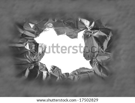 hole torn in a piece of metal, closeup - stock photo