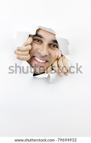 Hole torn in paper with smiling man looking through - stock photo