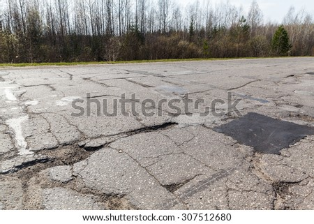 Holes and cracks in the asphalt road on bad broken in Russia - stock photo