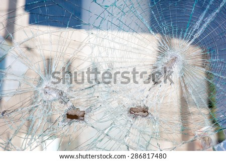 holes from shots in the shop window. - stock photo