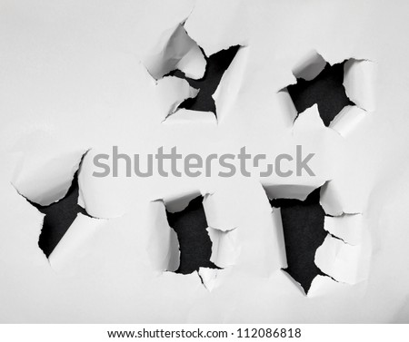 Holes torn and ripped into white paper. - stock photo