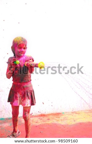 Holi celebrations - Young little girl playing with pichkaari on Holi in India. - stock photo