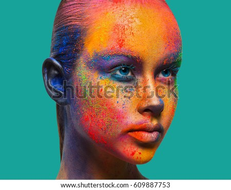 Holi festival of colors background. Female face art with creative make up. Closeup studio portrait of young fashion model isolated on turquoise background with bright colorful mix of paint