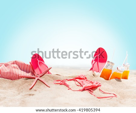 Holiday Accessories on Sand Beach Orange Juice Bikini Slippers Sea Star Sunny Summer Day Relax Concept Art Collage isolated Blue Background - stock photo