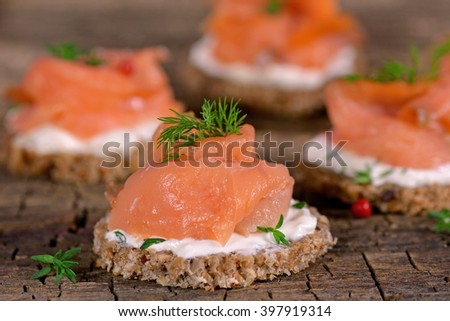Holiday appetizer canapes with smoked  salmon  on a wooden background - stock photo
