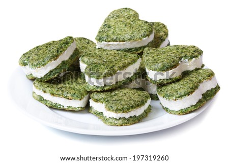 Holiday appetizer of green spinach pastries with cream cheese in the shape of heart isolated on white background  - stock photo