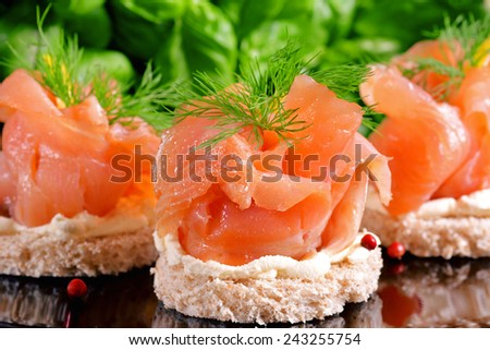 Holiday appetizer with salmon canapes on a background - stock photo