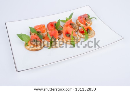 Holiday appetizer with salmon on white plate - stock photo