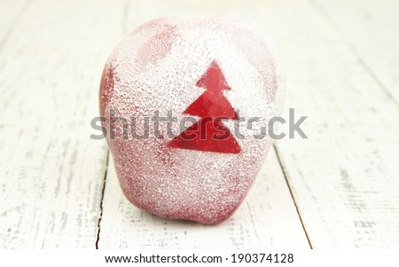 Holiday apple with frosted Christmas tree on wooden background - stock photo
