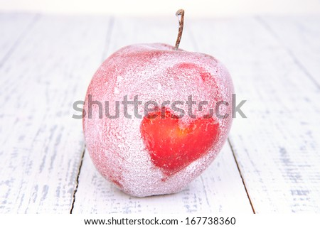 Holiday apple with frosted heart on wooden background - stock photo