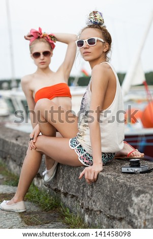 Holiday at the seaside. Two beautiful young women are relaxing on a pier near yachts. Outdoor, lifestyle - stock photo