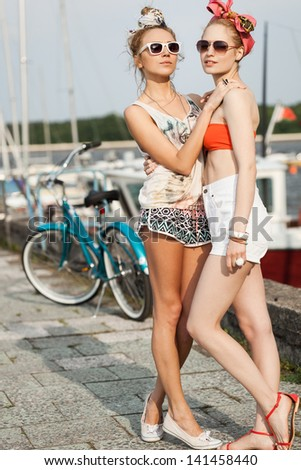 Holiday at the seaside. Young fashion women looking away on a pier near yachts. Outdoor, lifestyle - stock photo
