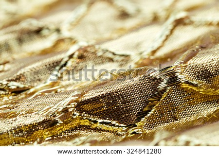 Holiday background image of gold sparkly mesh ribbon on metallic fabric with copy space. Macro with extremely shallow dof. - stock photo