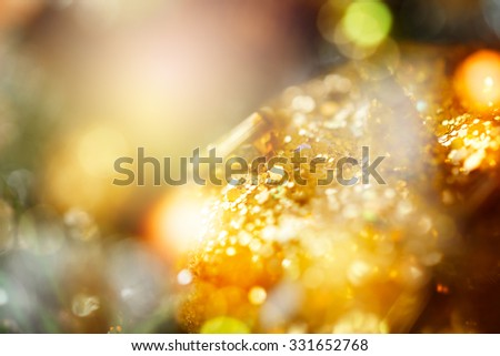Holiday Background with Blurred Christmas Lights and Glitters. Bright Gold Colors. Selective Focus. - stock photo