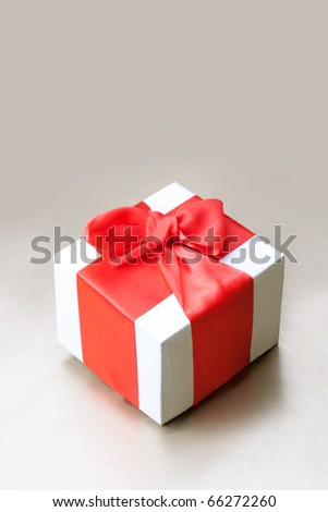 Holiday background with gift box and red ribbon. Still life.