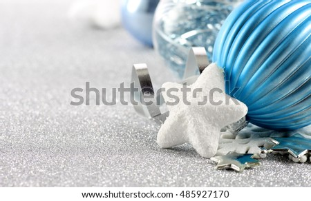 Holiday background with white snowflake and blue Christmas ornament