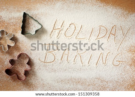 Holiday baking background image with christmas cookie cutters and words written in flour dusted on wooden pastry board. - stock photo
