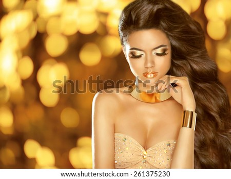 Holiday Beauty Fashion brunette girl with Long wavy hair, beauty makeup, luxury jewelry.  Model in dress posing over lights glitter bokeh background.