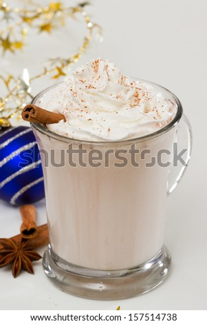 Holiday beverage on a white table with christmas decorations and spices