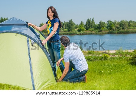 Holiday camping - Man And Woman Couple Setting Up Tent In The Countryside - stock photo