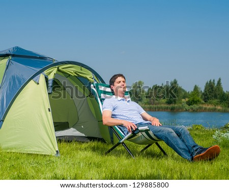 Holiday camping - Young man resting in a chaise lounge near A Tent In The Countryside - stock photo