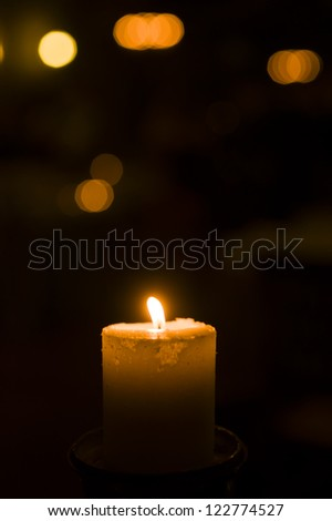Holiday candle with blurred lights in background
