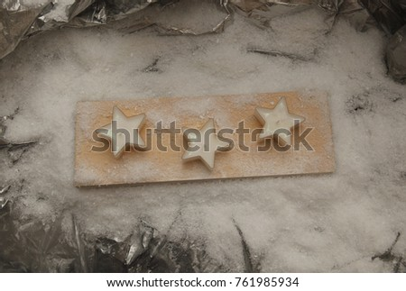 holiday candles in the shape of stars on a light wooden plaque in the snow