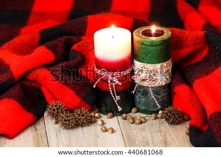 Holiday candles with candy cane striped ribbon by acorns and red and black winter wool blanket on antique rustic wood background - stock photo