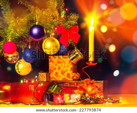 Holiday card of christmas tree and ornaments. Happy holiday. Shiny objects. Gift boxes and candle light with garlands